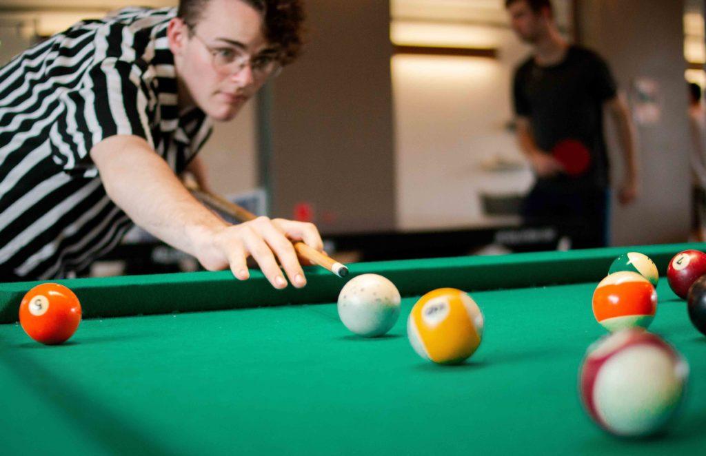 un jeune homme qui joue au billard