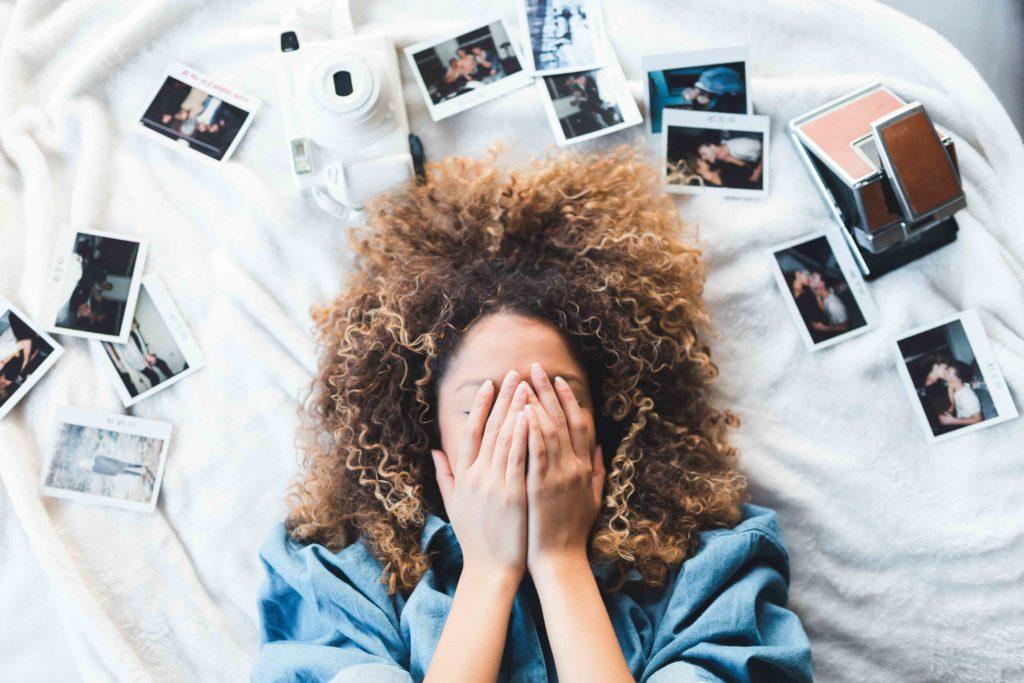 une femme allongée entourée de photos souvenirs